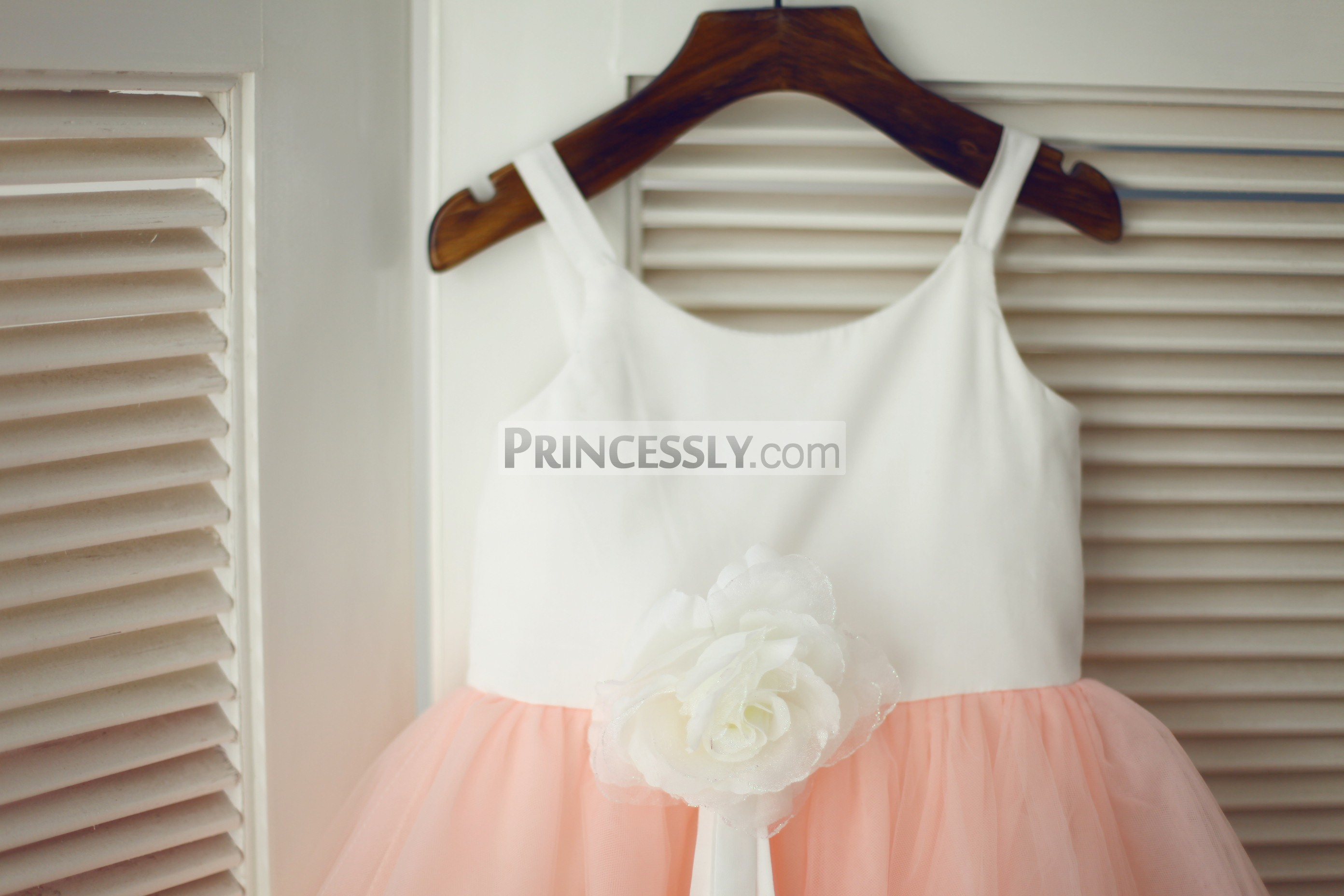 Thin straps scoop neckline of ivory cotton bodice with a flower