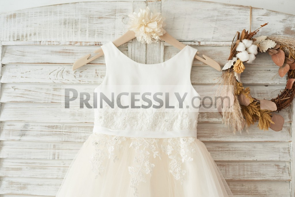Scoop neckline sleeveless bodice with satin belt and beaded ivory lace