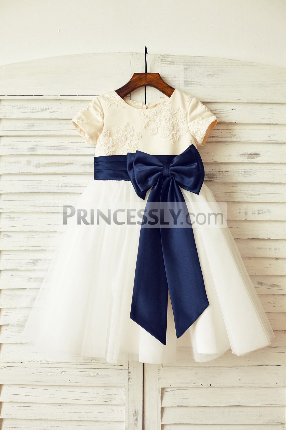 Ivory lace tulle flower girl dress with navy blue belt and bow