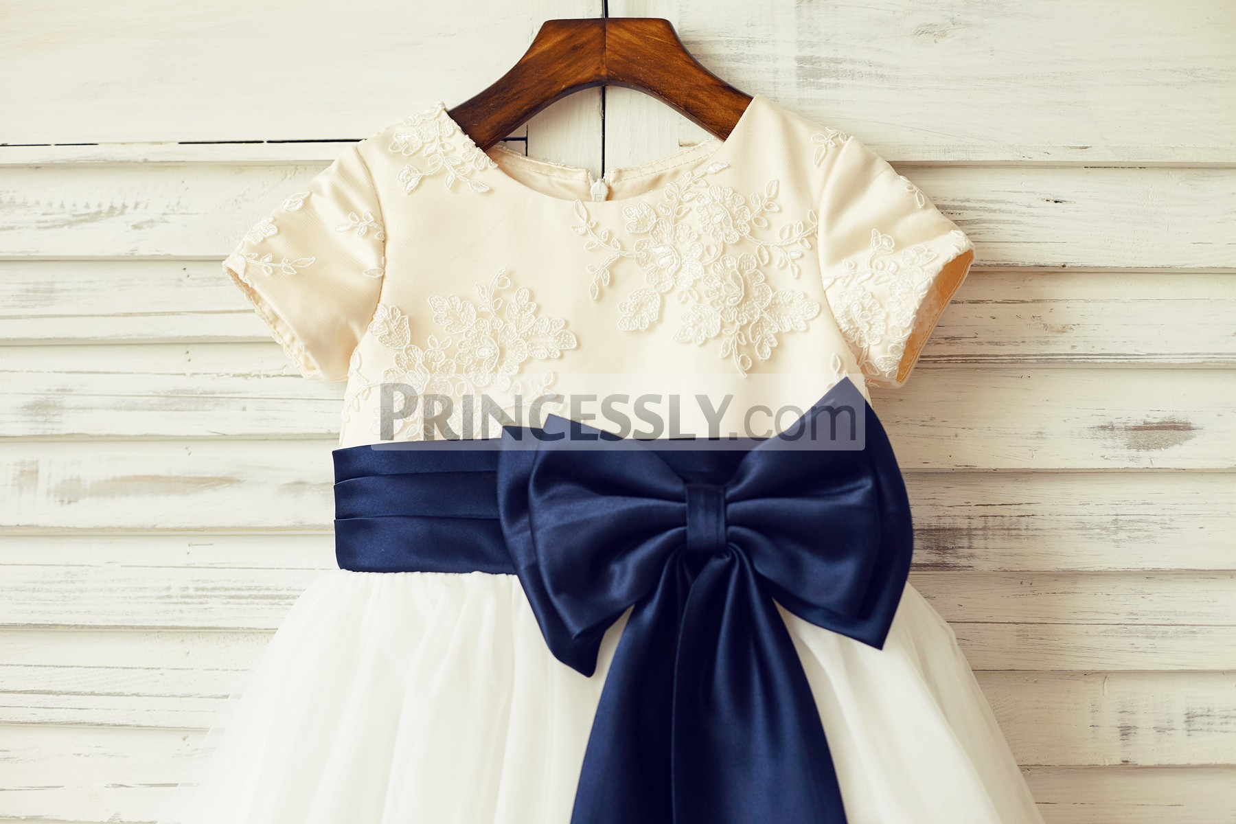 Sheer ivory lace bodice with champagne satin lining and navy blue belt and bow